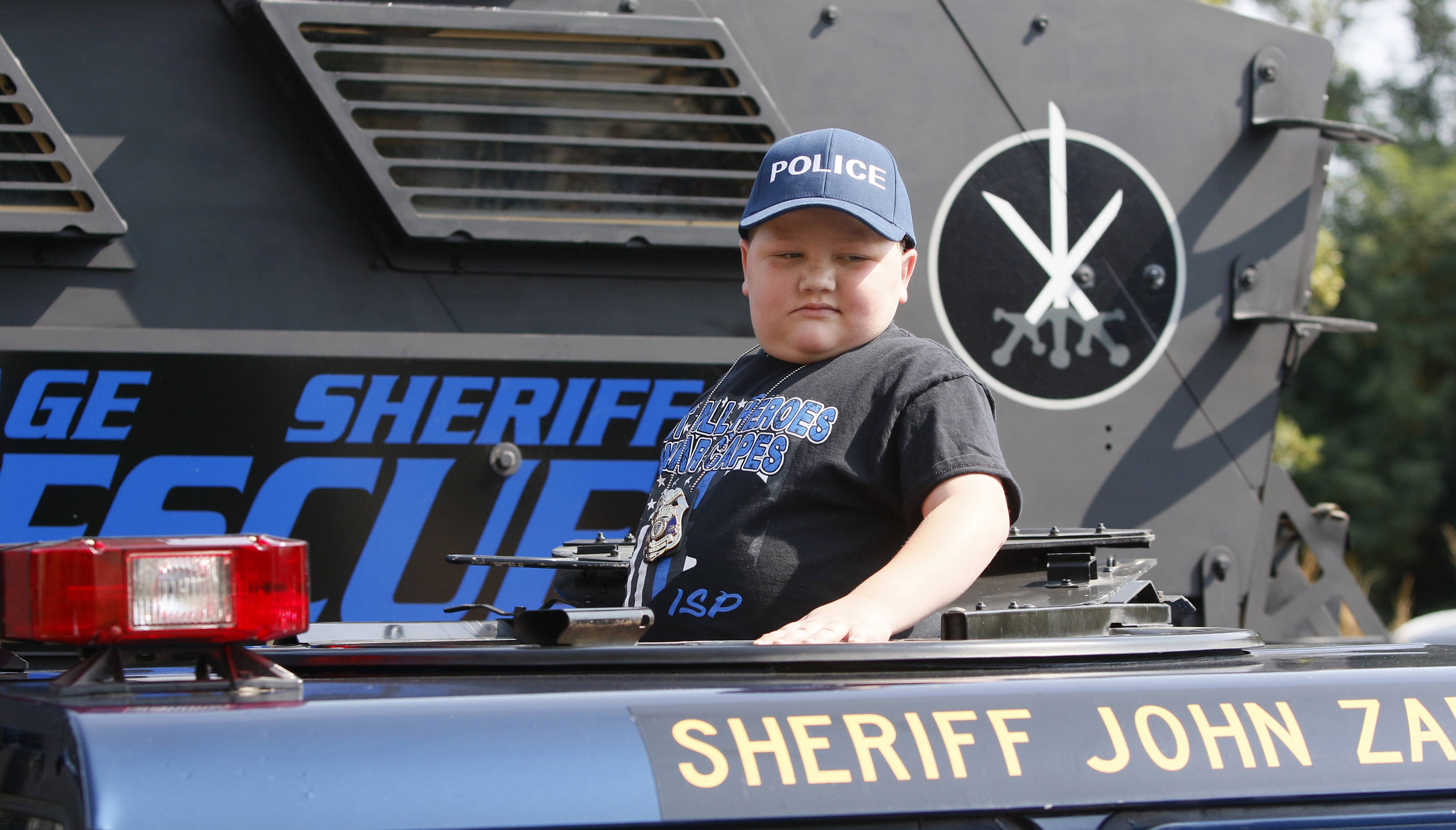 "Drake Price, 11, of Warsaw, Indiana, rides a DuPage County sheriff's office Humvee Tuesday, when he was sworn in as a junior deputy for the day. Drake, who has been receiving treatment for a benign brain tumor at Northwestern Medicine Chicago Proton Center in Warrenville, found the day ""exciting"" because he wants to be a police officer."