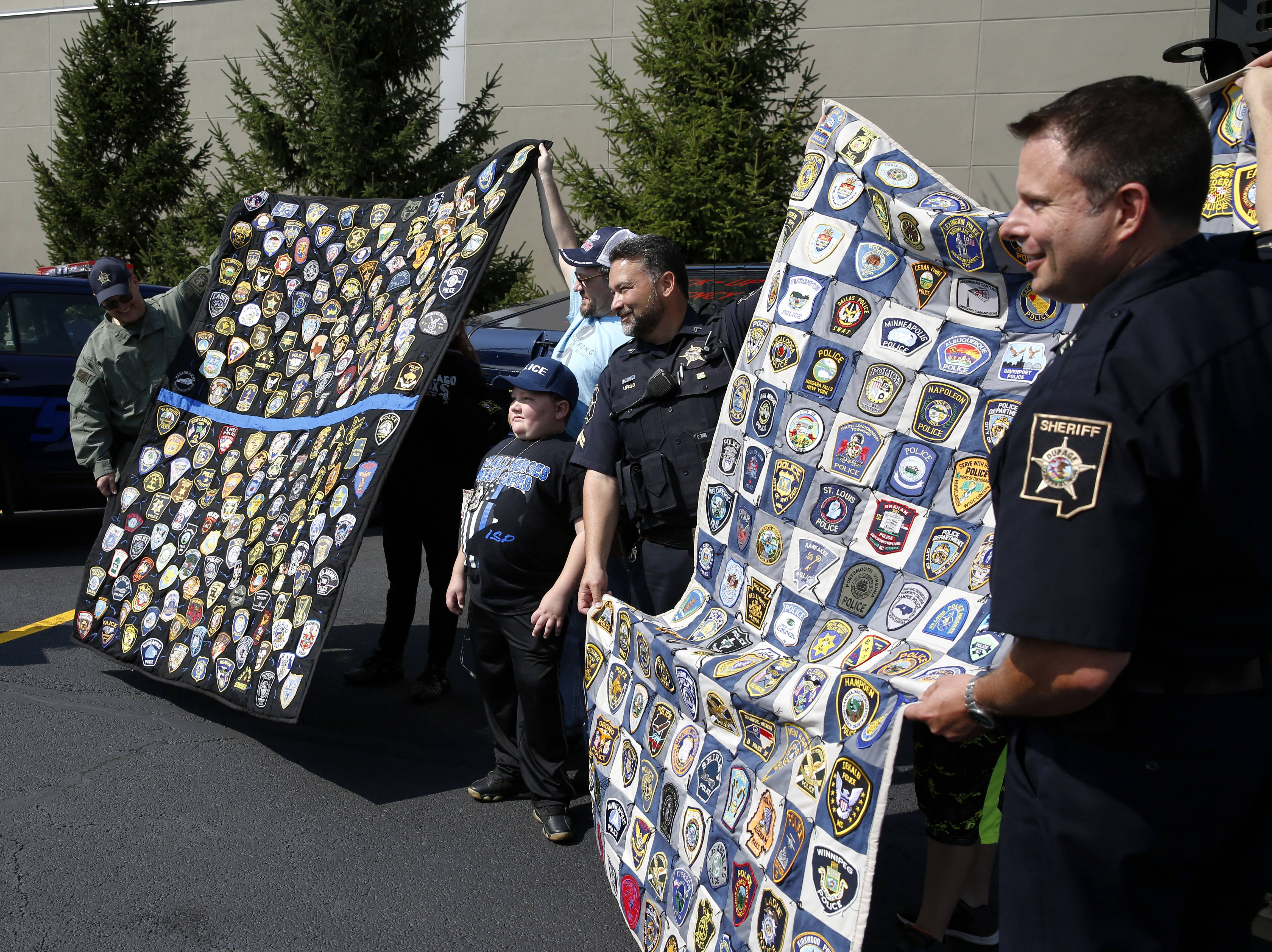 DuPage County sheriff's office personnel display more than 300 of the 2,500-plus police patch collection amassed by Drake Price, an Indiana 11-year-old who is receiving treatment for a benign brain tumor the size of a baseball at Northwestern Medicine Chicago Proton Center in Warrenville.