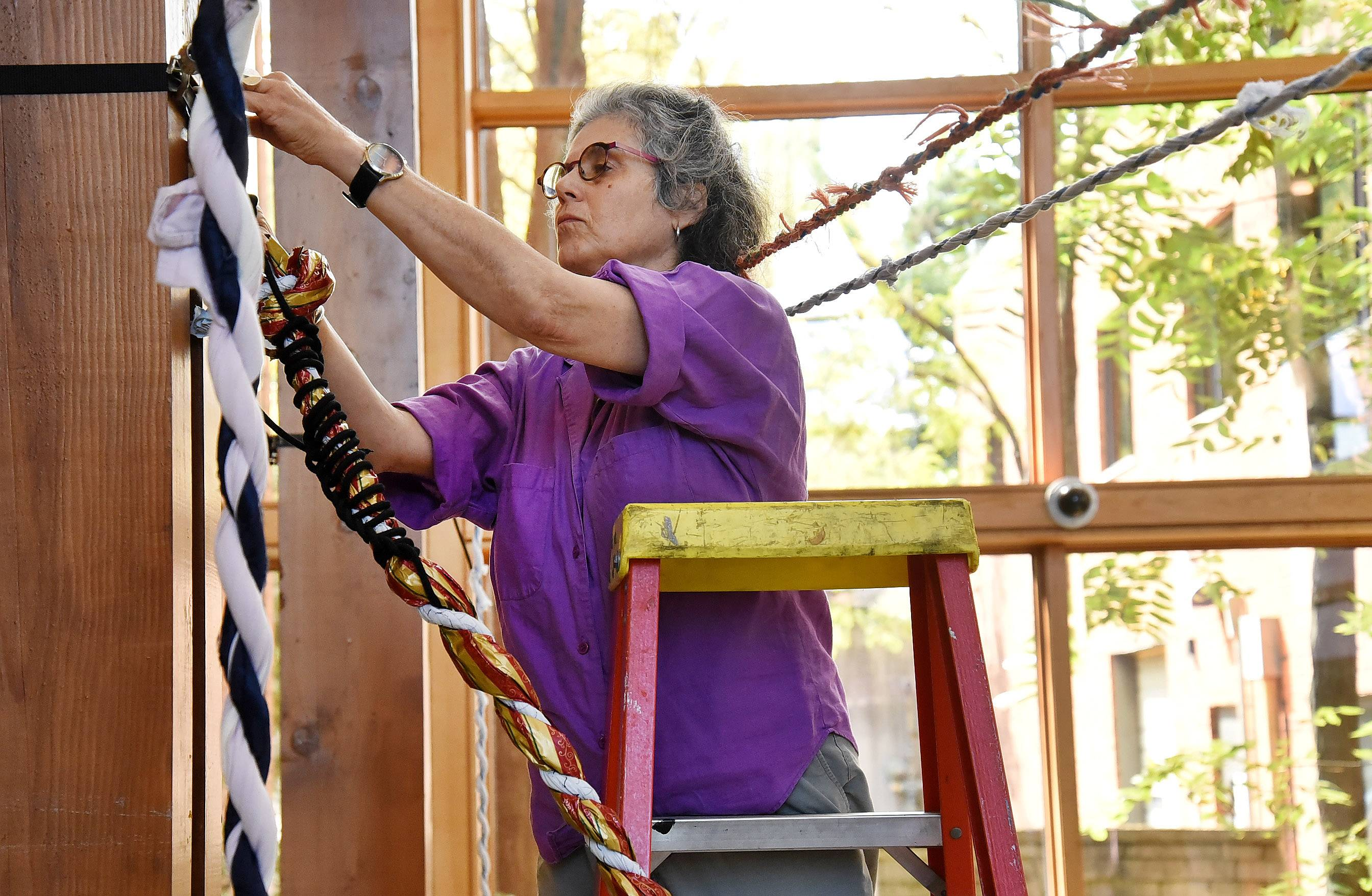 Chicago artist Barbara Cooper attaches sturdy ropes to the atrium's wooden pillars for an extensive web at Barrington Area Library.