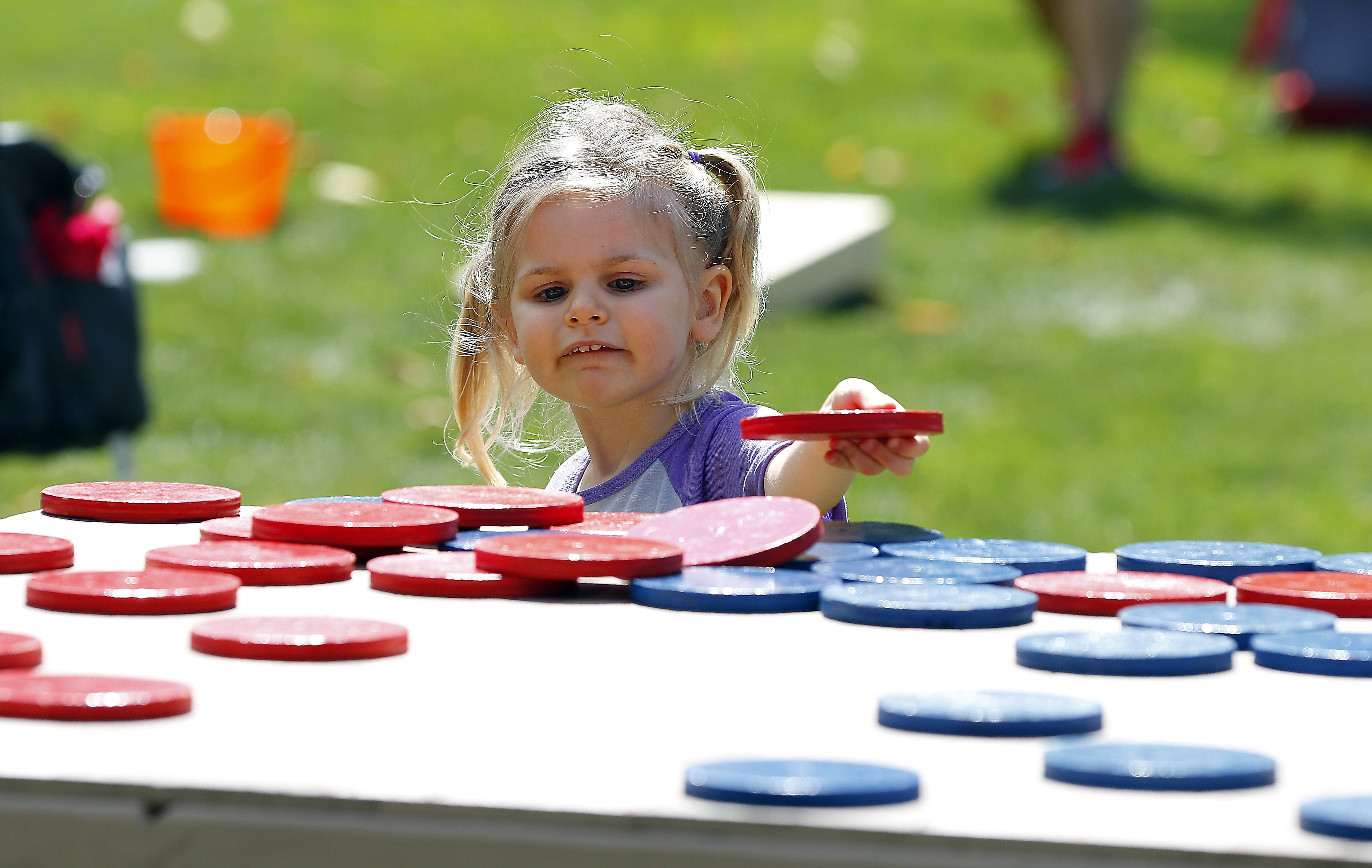 Kaela Leimberer, 2, of Wheaton plays a giant game of checkers during Heritage Fest in West Dundee.
