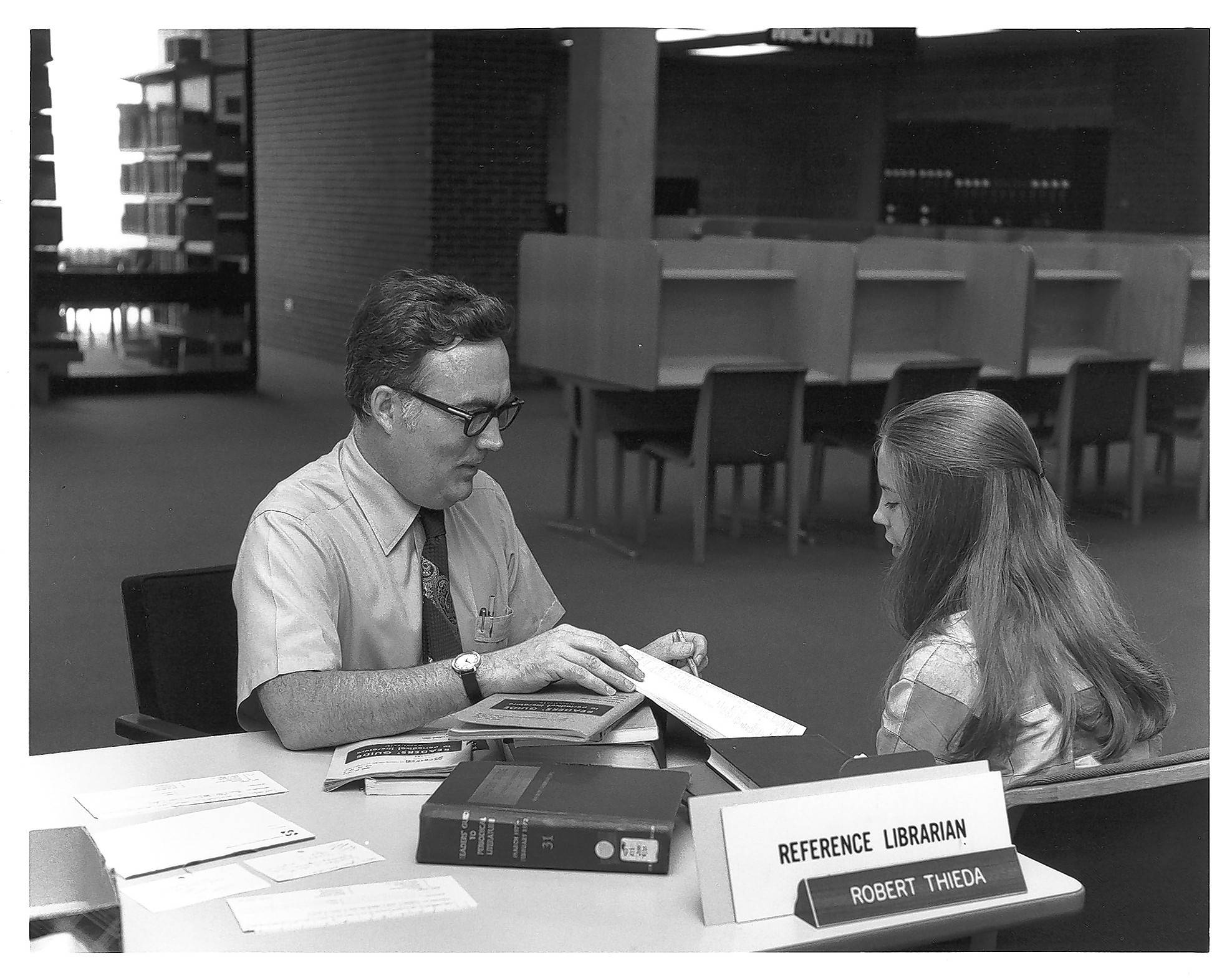 Robert Thieda, one of the original faculty members at Harper College, talks with a student in the early days of the college library.