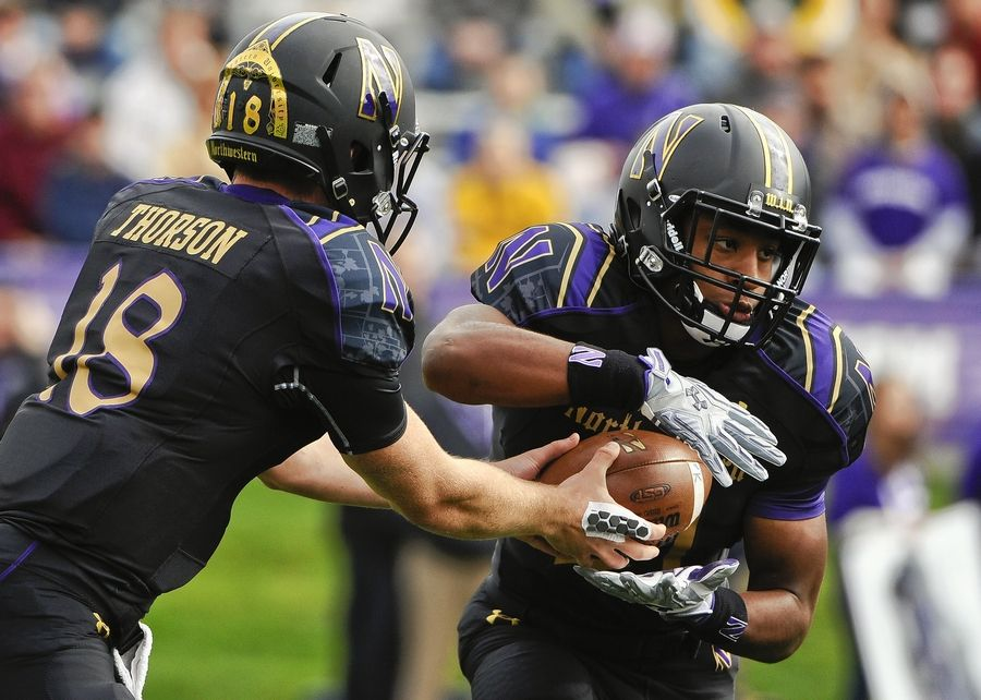 Northwestern quarterback Clayton Thorson (18) has handed the ball often to running back Justin Jackson (21) in his collegiate career. Jackson is poised to become the school's all-time leading rush. Jackson played at Glenbard North and Thorson at Wheaton North.