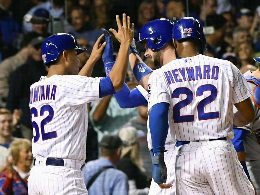 Kris Bryant, center, celebrates with Jose Quintana (62) and Jason Heyward (22) after they score on Bryant's 3-run homer against the New York Mets in the fourth inning at Wrigley Field on Friday.