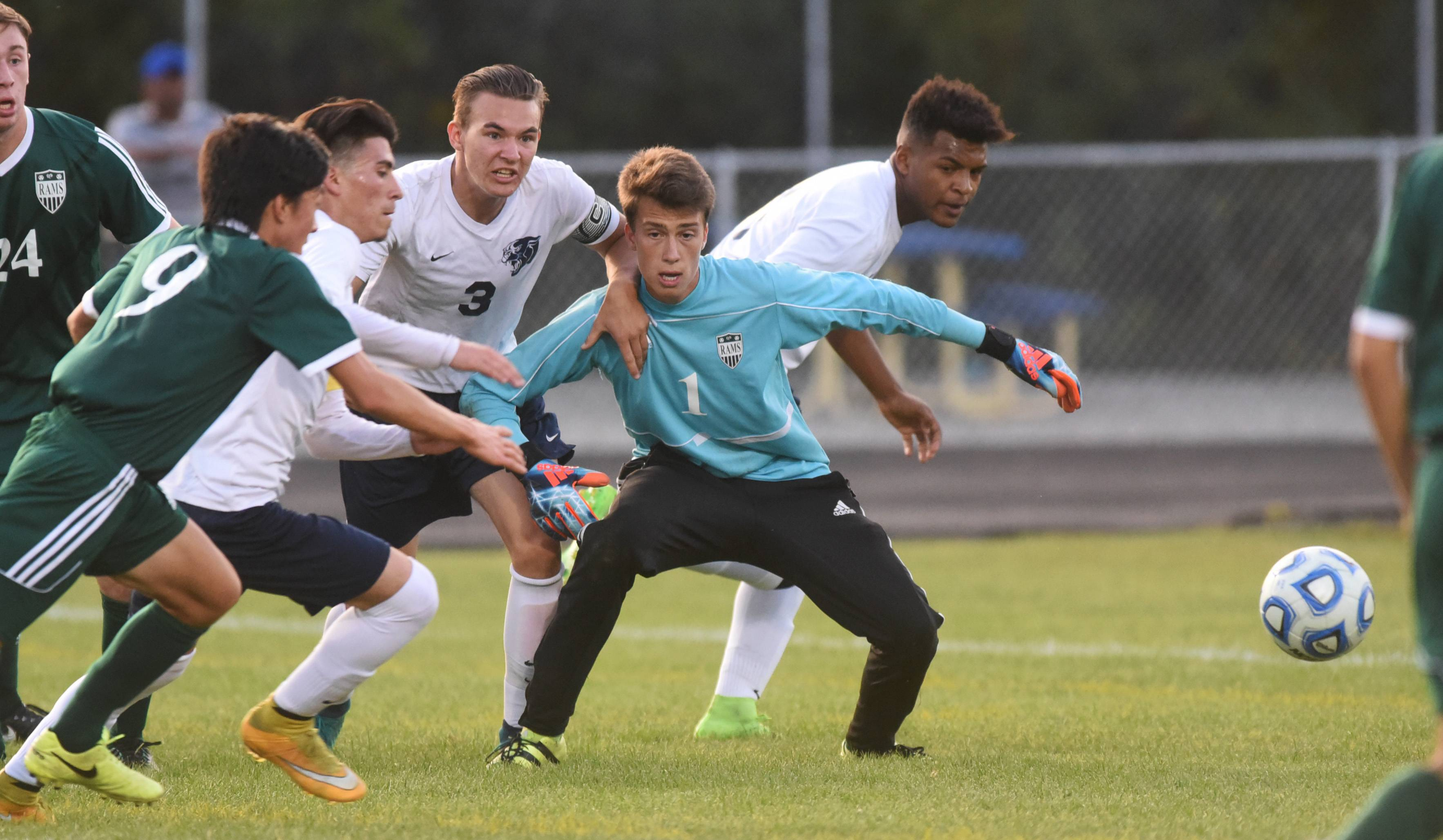 Grayslake Central goalkeeper Greg Madjarov (1) fights off Round Lake's Christofer Gomez, second from left, Jakub Bialkowski (3) and Maqiis Hayward, right, during Tuesday's soccer match in Round Lake.