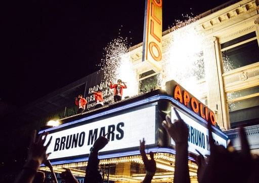 "This image released by CBS shows Bruno Mars, center, during the taping a TV special on top of the Apollo Theater marquee in New York. Atlantic Records and CBS announced Tuesday, Sept. 12, 2017, that ""BRUNO MARS: 24K MAGIC LIVE AT THE APOLLO� will air Nov. 29 on CBS. (CBS via AP)"