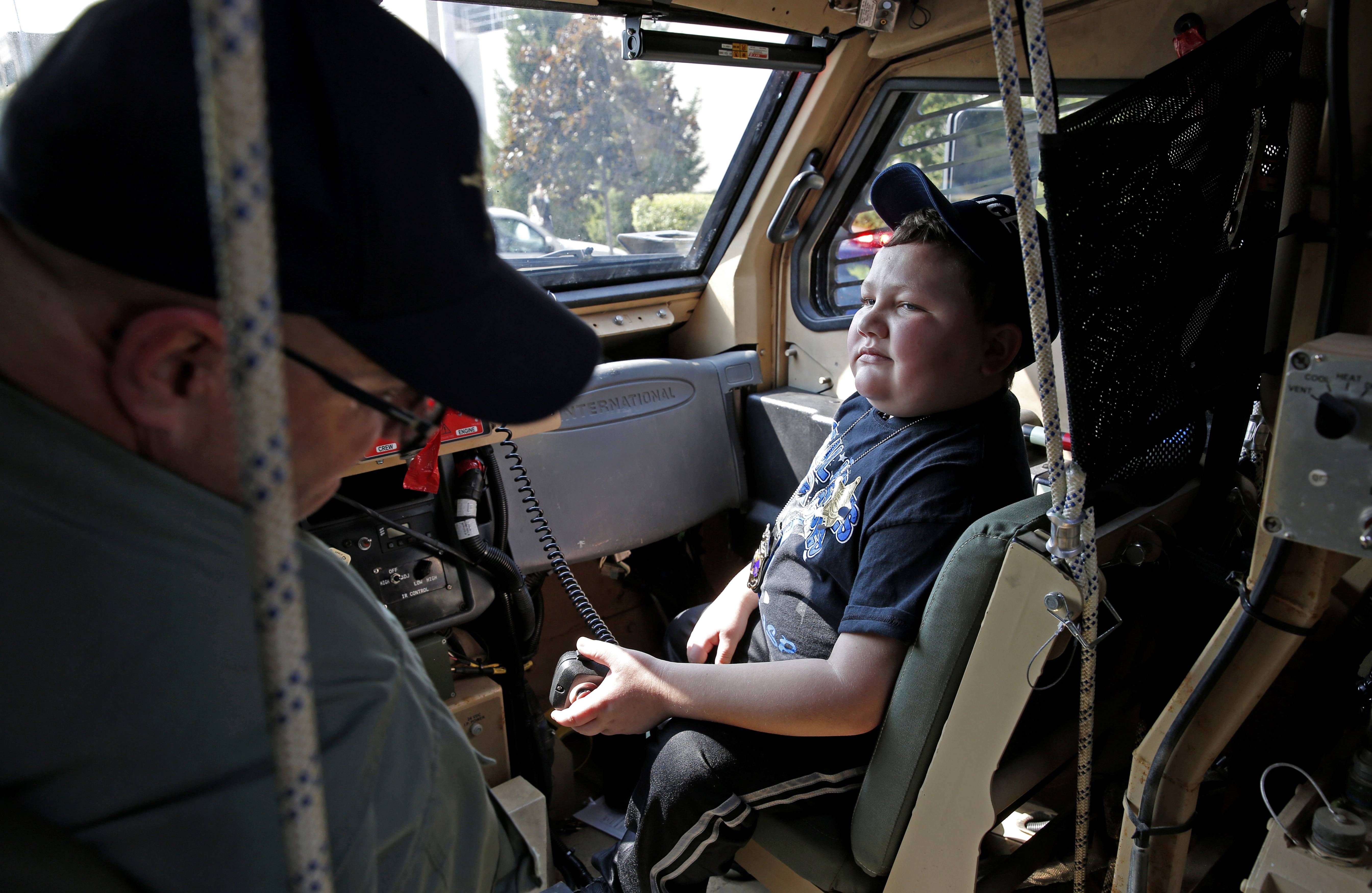 Drake Price, an 11-year-old patient who is receiving treatment for a brain tumor at the Northwestern Medicine Chicago Proton Center in Warrenville, takes front seat Tuesday in an armored personnel carrier from the DuPage County sheriff's office's SWAT team under the direction of Special Operations Sgt. Tom Hoffman.