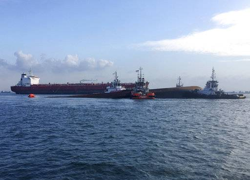 This photo provided by the Maritime and Port Authority of Singapore, four tug boats moving the partially submerged dredger safely to an area near Pulau Senang, Singapore, for follow up underwater search operations, Wednesday, Sept. 13, 2017. An oil tanker and a dredger collided in Singapore waters Wednesday, capsizing the dredger and leaving five of its crew missing, authorities said. The dredger was left partially submerged and an underwater search and rescue operation was underway on the vessel, the Maritime and Port Authority of Singapore said. (The Maritime and Port Authority of Singapore via AP)
