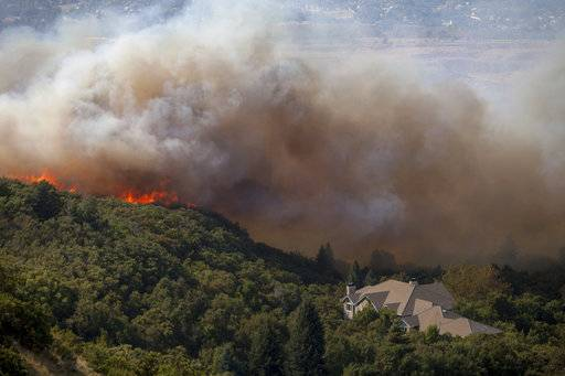 "FILE- In this Sept. 5, 2017, file photo, a wildfire burns through residential areas near the mouth of Weber Canyon near Ogden, Utah. Interior Secretary Ryan Zinke is directing all land managers and park superintendents to be more aggressive in cutting down small trees and underbrush to prevent wildfires. In a memo on Tuesday, Sept. 12, Zinke said the Trump administration will take a new approach and work proactively to prevent fires ""through aggressive and scientific fuels reduction management� to save lives, homes and wildlife habitat. (Benjamin Zack/Standard-Examiner via AP, File)"