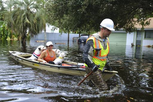 Cory Donoher pulls Linda DeWalt and her dogs on his kayak down a street in Jacksonville, Fla., Monday, Sept. 11, 2017, after it was flooded from the Ortega River when Hurricane Irma passed over the region. (Dede Smith/The Florida Times-Union via AP)