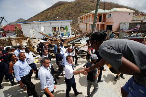 France's President Emmanuel Macron shakes hands with residents during his visit in the French Caribbean islands of St. Martin , Tuesday, Sept. 12, 2017. Macron is in the French-Dutch island of St. Martin, where 10 people were killed on the French side and four on the Dutch. (AP Photo/Christophe Ena, Pool)