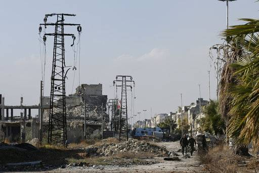 In this Dec. 4, 2016 photo, Syrian army soldiers walk next to damaged electricity transmission towers on their way back from the frontline of fighting, in Karam al-Tarab neighborhood of Aleppo, Syria. Syrian state news says the government has signed a contract to import Iranian power plants for the country's war-battered city of Aleppo, an early sign of the major role Tehran is expected to play in Syria's reconstruction. (AP Photo/Hassan Ammar)