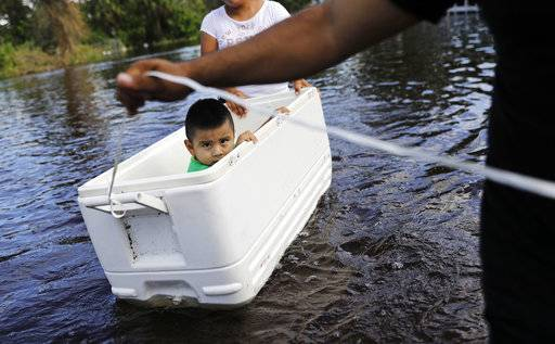 Alfonso Jose Jr., 2, is floated down his flooded street by his parents as the wade through water to reach an open convenience store in the wake of Hurricane Irma in Bonita Springs, Fla., Tuesday, Sept. 12, 2017. (AP Photo/David Goldman)