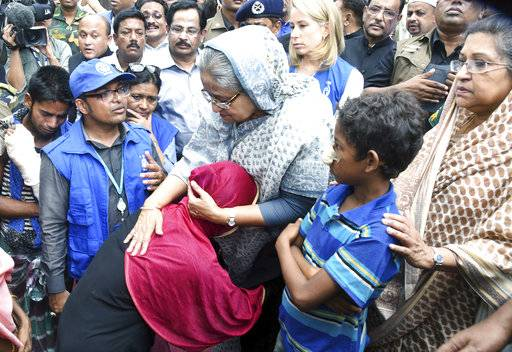 Bangladeshi Prime Minister Sheikh Hasina, center, meets with Rohingya Muslims at Kutupalong refugee camp, near the border town of Ukhia, Bangladesh, Tuesday, Sept. 12, 2017. Hasina visited the struggling refugee camp that has absorbed some of the hundreds of thousands of Rohingya who fled recent violence in Myanmar, a crisis she said left her speechless. (AP Photo/Saiful Kallol)