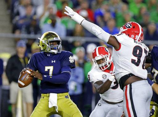 Notre Dame quarterback Brandon Wimbush (7) looks to throw over Georgia nose tackle John Atkins (97) during the first half of an NCAA college football game in South Bend, Ind., Saturday, Sept. 9, 2017. (AP Photo/Michael Conroy)