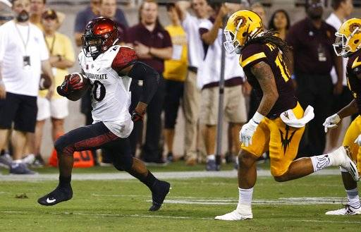 San Diego State's Rashaad Penny, left, runs for a first down as Arizona State's J'Marcus Rhodes, right, tries to chase Penny down during the second half of an NCAA college football game Saturday, Sept. 9, 2017, in Tempe, Ariz. San Diego State defeated Arizona State 30-20. (AP Photo/Ross D. Franklin)