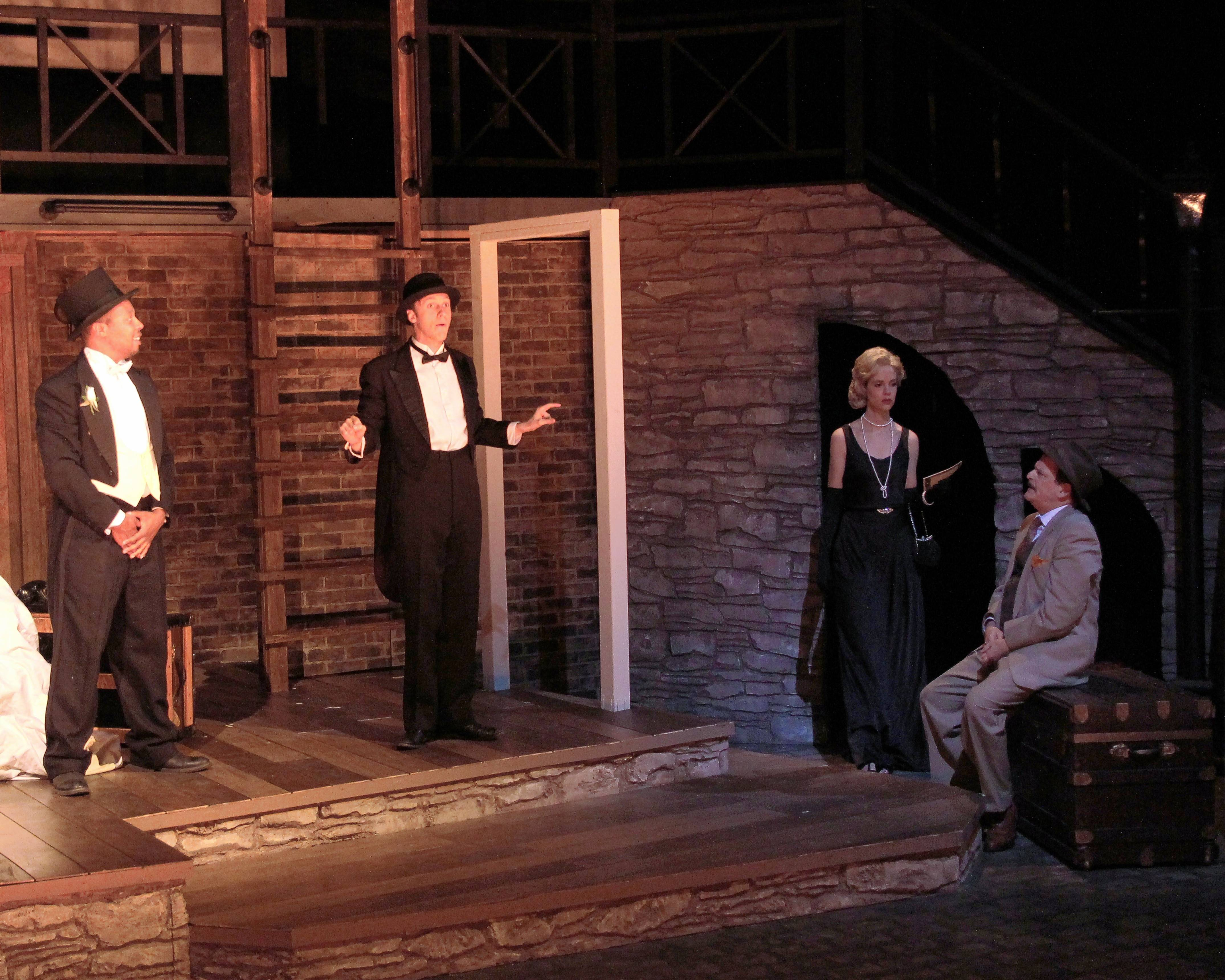 "Richard Hannay (Bryan Burke), right, meets a cool, Hitchcockian blonde (Rebecca Cox) during a theatrical performance by Mr. Memory (Daniel Millhouse), second from left, and his Compère (Matthew Singleton), left, in Buffalo Theatre Ensemble's ""The 39 Steps."""