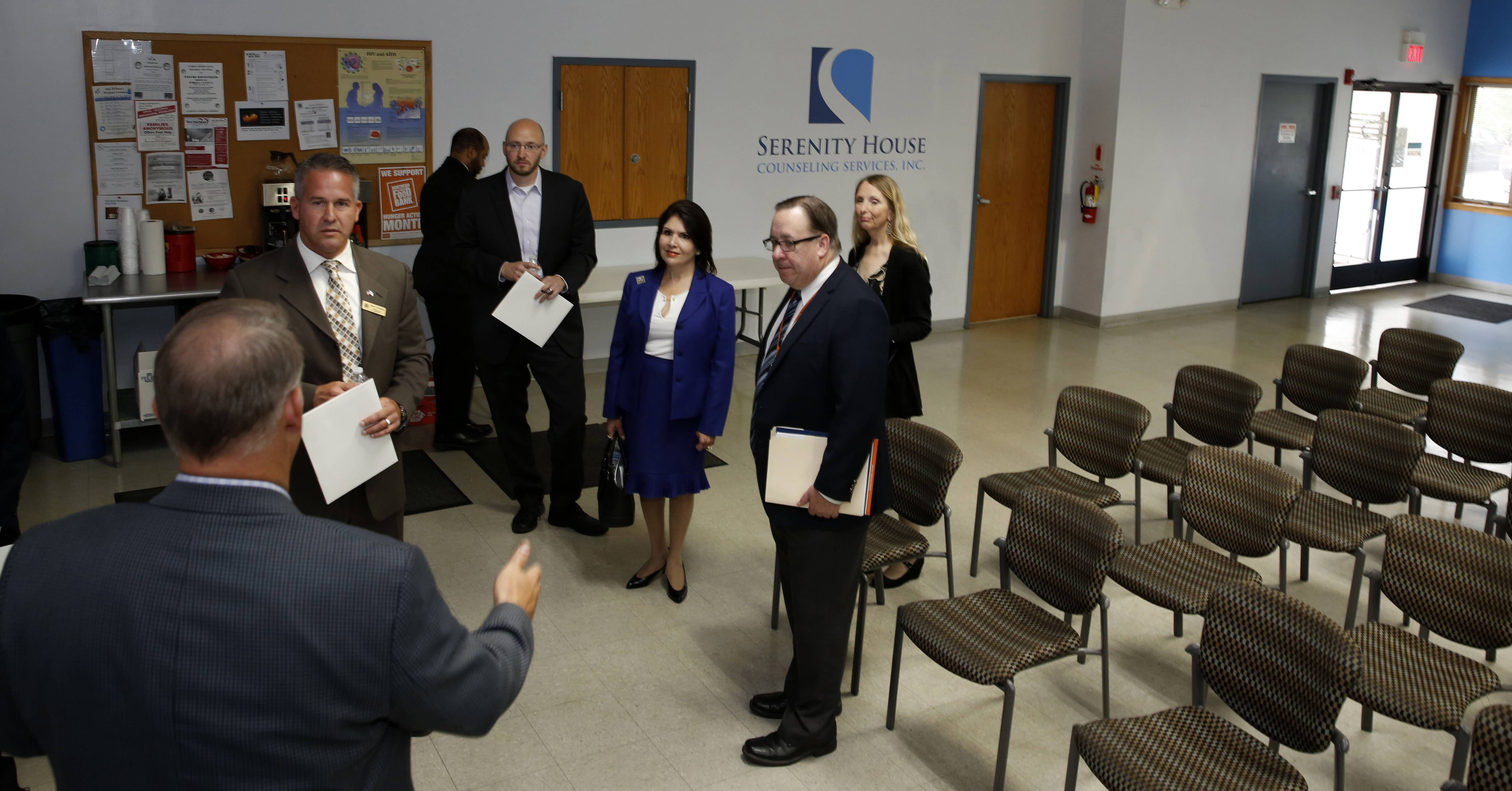 Mark Buschbacher, executive director of Serenity House Counseling Services, left, shows Lt. Gov. Evelyn Sanguinetti, center, and other officials a meeting space on the drug and alcohol recovery company's Addison campus. Serenity House offers a 90-day residential program, but Buschbacher said he fears many recovering opioid addicts are not able to take enough time for their treatment.
