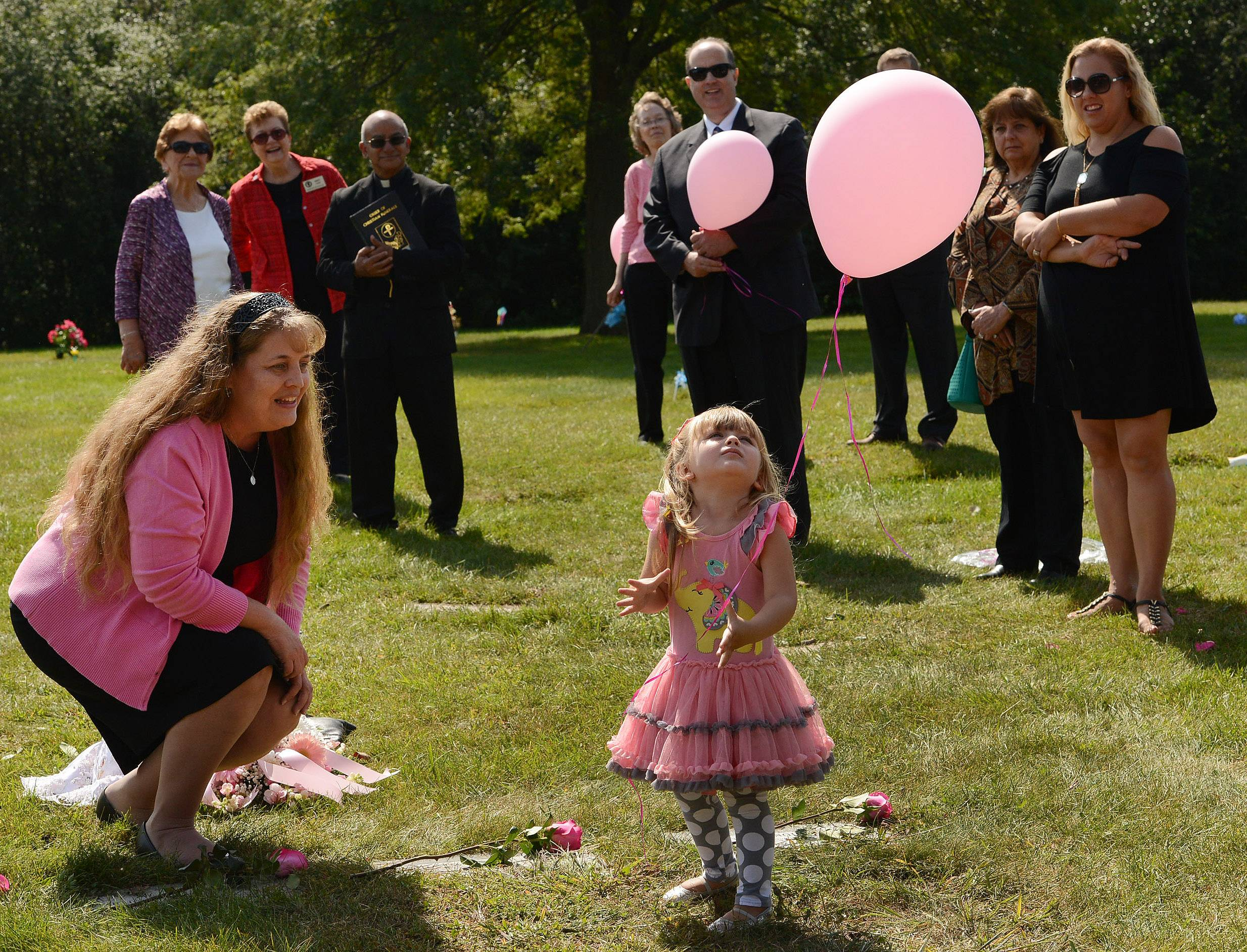 Susan Walker of Rest in His Arms helps 2½-year-old Trinity Haack of Roselle, who was left at a safe haven as a baby and has since been adopted, release a balloon at the gravesite of babies Mariam Jane Uddin and Ariyah Mikayla Hoover at All Saints Cemetery in Des Plaines.