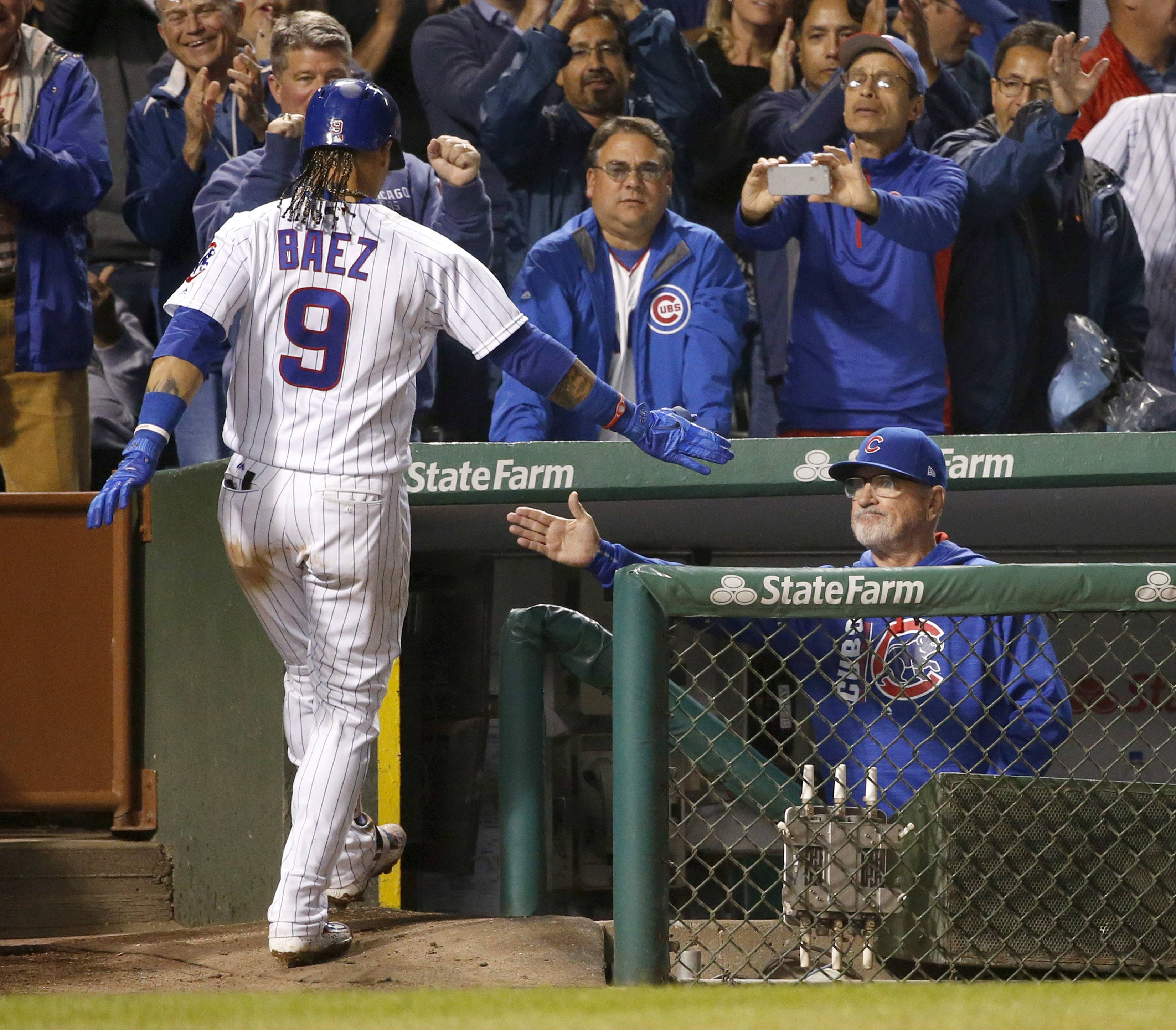 Chicago Cubs manager Joe Maddon, right, greets Javier Baez at the dugout after Baez's home run off New York Mets relief pitcher Chasen Bradford during the seventh inning of a baseball game Wednesday, Sept. 13, 2017, in Chicago. (AP Photo/Charles Rex Arbogast)