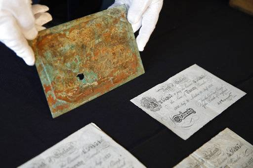 H. Keith Melton holds a printing plate for printing high quality counterfeit notes of British currency used by the Nazi's during World War II, along with three examples of counterfeit notes, which are among his donations to the International Spy Museum from his collection of spy objects, Wednesday, Sept. 13, 2017, in Washington.