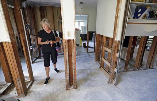 In this Monday, Sept. 11, 2017, photo, Arlene Estle looks at the damage to her home which was flooded in the aftermath of Hurricane Harvey, in Houston. Victims of Harvey, desperate to rebuild their homes and lives, are facing the harsh reality that it may take months for an overwhelmed construction industry to address their needs.