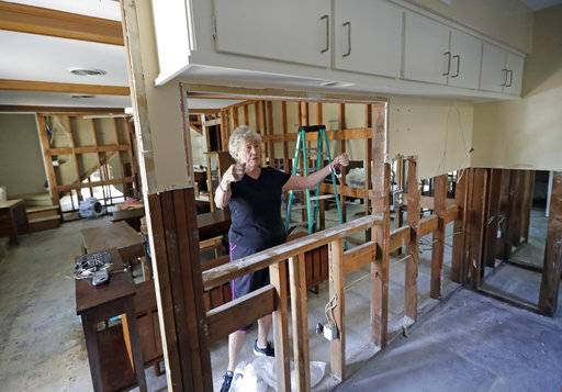 In this Monday, Sept. 11, 2017, photo, Arlene Estle talks about the damage to her home caused by floodwaters from Hurricane Harvey, in Houston. Victims of Harvey, desperate to rebuild their homes and lives, are facing the harsh reality that it may take months for an overwhelmed construction industry to address their needs.