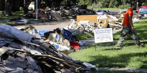 In this Monday, Sept. 11, 2017, photo, a remodeling sign sits in a yard outside a home damaged by floodwaters from Hurricane Harvey, in Houston. Victims of Hurricane Harvey, desperate to rebuild their homes and lives, are facing the harsh reality that it may take months for an overwhelmed construction industry to address their needs.