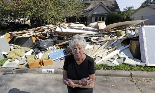 In this Monday, Sept. 11, 2017, photo, Arlene Estle stands outside her home which was damaged by floodwaters from Hurricane Harvey, in Houston. Victims of Harvey, desperate to rebuild their homes and lives, are facing the harsh reality that it may take months for an overwhelmed construction industry to address their needs.