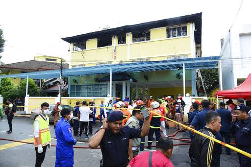Police and rescue personnel work at an Islamic religious school cordoned off after the fire on the outskirts of Kuala Lumpur  Thursday, Sept. 14, 2017.  A fire department official in Malaysia said a fire at the Islamic religious school has killed people, mostly teenagers.