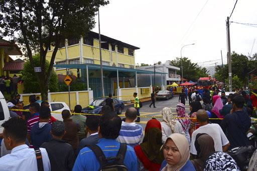 People gather outside an Islamic religious school which was cordoned off after the fire on the outskirts of Kuala Lumpur  Thursday, Sept. 14, 2017. A fire department official in Malaysia said a fire at the Islamic religious school has killed people, mostly teenagers.