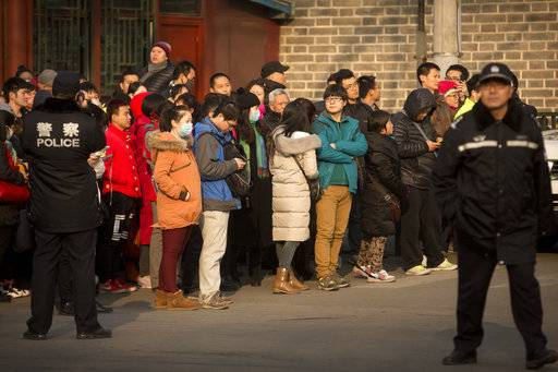 FILE - In this Jan. 1, 2016, file photo, policemen watch as depositors from Ezubo gather outside the State Bureau for Letters and Calls Reception Division office in Beijing. The founder of a Chinese online peer-to-peer lender has been sentenced to life in prison Tuesday, Sept. 12, 2017, on charges he defrauded investors of $7.7 billion in one of China's biggest financial scams. (AP Photo/Mark Schiefelbein, File)