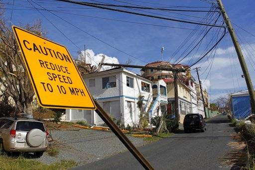 A speed limit sign stands tilted and a power line that snapped it half lays on a building, after the passage of Hurricane Irma in Charlotte Amalie, St. Thomas, U.S. Virgin Islands, Sunday, Sept. 10, 2017. The storm ravaged such lush resort islands as St. Martin, St. Barts, St. Thomas, Barbuda and Anguilla. (AP Photo/Ricardo Arduengo)
