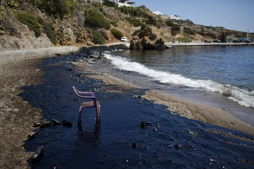 A plastic chair stands on a polluted beach by a big oil spillage on the island of Salamina, near Athens, on Tuesday, Sept. 12, 2017. Greece's merchant marine minister says clean-up crews are working to contain pollution caused after the small tanker Agia Zoni II sank off Salamina on Sunday, Sept. 10, with a cargo of 2,200 tons of fuel oil and 370 tons of marine gas oil. (AP Photo/Petros Giannakouris)