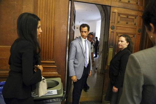 Anthony Weiner, center, and Huma Abedin, left, prepare to leave the courtroom in New York on Wednesday, Sept. 13, 2017. The couple asked a New York City judge for privacy in their divorce case. (Jefferson Siegel/The Daily News via AP, Pool)