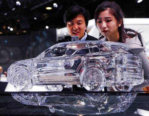 Asian visitors look at a model of a Porsche Cayenne on the second Media day of the IAA Motor Show in Frankfurt, Germany, Wednesday, Sept. 13, 2017. From frighteningly fast hypercars to new electric SUVs, the Frankfurt auto show is a major event for car lovers wanting to get a glimpse of the future.