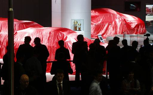 Visitors wait for the Ferrari presentation during the first media day of the International Frankfurt Motor Show IAA in Frankfurt, Germany, Tuesday, Sept. 12, 2017, which runs through Sept. 24, 2017. From frighteningly fast hypercars to new electric SUVs, the Frankfurt auto show is a major event for car lovers wanting to get a glimpse of the future.