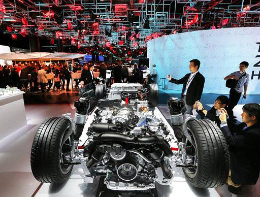 Visitors take photographs of the chassis of an Audi A8 plug-in-hybrid on the second media day of the IAA Motor Show in Frankfurt, Germany, Wednesday, Sept. 13, 2017. From frighteningly fast hypercars to new electric SUVs, the Frankfurt auto show is a major event for car lovers wanting to get a glimpse of the future.