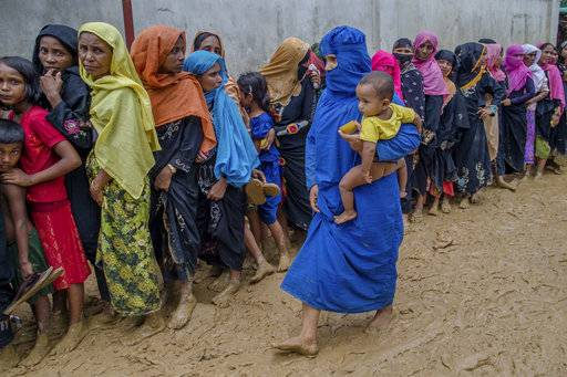 Newly arrived Rohingya women wait for their turn to collect building material for their shelters distributed by aid agencies in Kutupalong refugee camp, Bangladesh, Wednesday, Sept. 13, 2017. With Rohingya refugees still flooding across the border from Myanmar, those packed into camps and makeshift settlements in Bangladesh were becoming desperate for scant basic resources as hunger and illness soared.