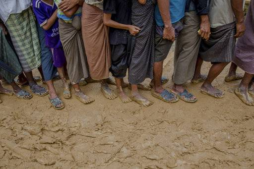 Newly arrived Rohingya wait for their turn to collect building material for their shelters distributed by aid agencies in Kutupalong refugee camp, Bangladesh, Wednesday, Sept. 13, 2017. With Rohingya refugees still flooding across the border from Myanmar, those packed into camps and makeshift settlements in Bangladesh were becoming desperate for scant basic resources as hunger and illness soared.