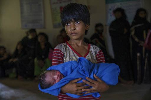 Rohingya Muslim girl Afeefa Bebi, who recently crossed over from Myanmar into Bangladesh, holds her few-hours-old brother as doctors check her mother Yasmeen Ara at a community hospital in Kutupalong refugee camp, Bangladesh, Wednesday, Sept. 13, 2017. The family crossed into Bangladesh on Sept. 3. Recent violence in Myanmar has driven hundreds of thousands of Rohingya Muslims to seek refuge across the border in Bangladesh. But Rohingya have been fleeing persecution in Buddhist-majority Myanmar for decades, and many who have made it to safety in other countries still face a precarious existence.