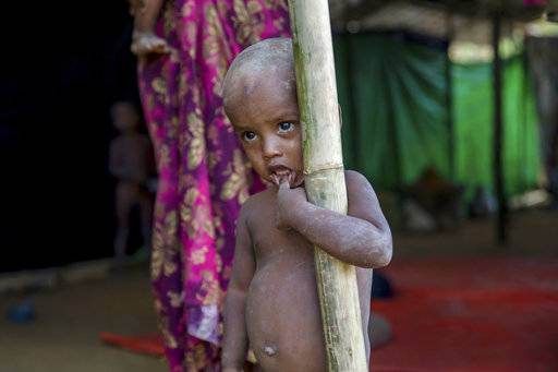 A Rohingya Muslim boy, who crossed over from Myanmar into Bangladesh, stands near a newly built shelter at Balukhali refugee camp, Bangladesh, Wednesday, Sept. 13, 2017. Recent violence in Myanmar has driven hundreds of thousands of Rohingya Muslims to seek refuge across the border in Bangladesh. But Rohingya have been fleeing persecution in Buddhist-majority Myanmar for decades, and many who have made it to safety in other countries still face a precarious existence.