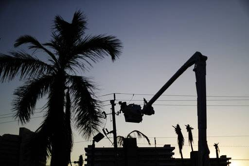 A worker is silhouetted against the setting sun as he works on a power line in the aftermath of Hurricane Irma in Marco Island, Fla., Tuesday, Sept. 12, 2017. Florida officials say crews are restoring power across the state, but 9.5 million people remain without electricity. State Emergency Management Center officials say they restored power to 1.7 million homes and businesses on Tuesday.