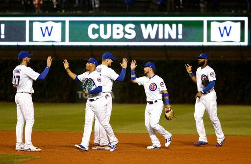 The Chicago Cubs celebrate the team's 17-5 win over the New York Mets in a baseball game Wednesday, Sept. 13, 2017, in Chicago.