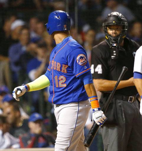 New York Mets' Juan Lagares (12) has words with home plate umpire Kerwin Danley after Danley called Lagares out on strikes during the third inning of a baseball game against the Chicago Cubs on Wednesday, Sept. 13, 2017, in Chicago.