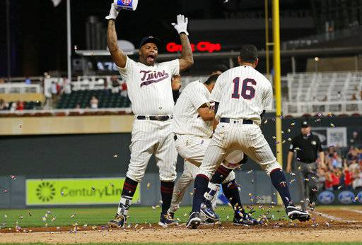 Minnesota Twins' Eddie Rosario, center, heads for home between bubble-gum-tossing Kennys Vargas, left, and Ehire Adrianza, right, as he scores on his two-run walk-off home run against the San Diego Padres during the 10th inning of a baseball game Wednesday, Sept. 13, 2017, in Minneapolis. The Twin won 3-1. AP Photo/Jim Mone)