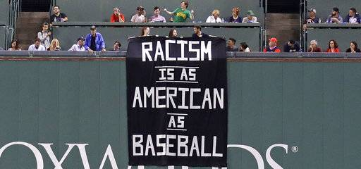 A banner is unfurled over the left field wall during the fourth inning of a baseball game between the Boston Red Sox and Oakland Athletics at Fenway Park in Boston, Wednesday, Sept. 13, 2017. (AP Photo/Charles Krupa)