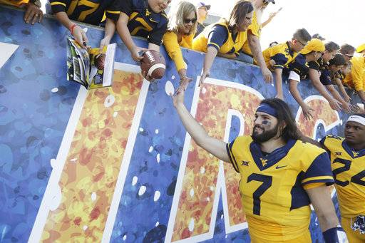 FILE - In this Saturday, Sept. 9, 2017, file photo, West Virginia quarterback Will Grier (7) celebrates their victory with fans at the conclusion of an NCAA college football game against East Carolina in Morgantown, W.Va.  Two years after a promising football career at Florida came crashing down, Will Grier is now the toast of West Virginia with two strong performances so far in the 2017 season. Yet he's not the most famous person in his family. Younger brothers Hayes and Nash are huge internet stars, building their own brands to millions of teenagers and young adults.