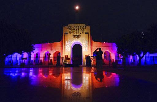 A visitor takes a photo of a blazing Olympic cauldron at the Los Angeles Memorial Coliseum on Wednesday, Sept. 13, 2017. The cauldron was lit early Wednesday morning at the stadium that was the site of the 1932 and 1984 Olympics. An International Olympic Committee meeting in Peru is to make it official that LA will host in 2028 and that the 2024 Games will go to Paris.