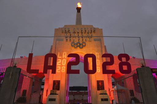 An LA2028 sign is seen in front of a blazing Olympic cauldron at the Los Angeles Memorial Coliseum on Wednesday, Sept. 13, 2017. The cauldron was lit early Wednesday morning at the stadium that was the site of the 1932 and 1984 Olympics. An International Olympic Committee meeting in Peru is to make it official that LA will host in 2028 and that the 2024 Games will go to Paris.