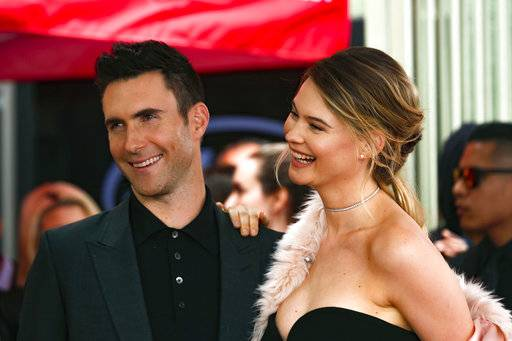 FILE - In this Feb. 10, 2017, file photo, Adam Levine, left, and his wife Behati Prinsloo smile at a ceremony that honored him with a star on the Hollywood Walk of Fame in Los Angeles. Levine's publicist confirmed to the AP on Sept. 14, 2017, that the couple is expecting a second child. (Photo by Willy Sanjuan/Invision/AP, File)